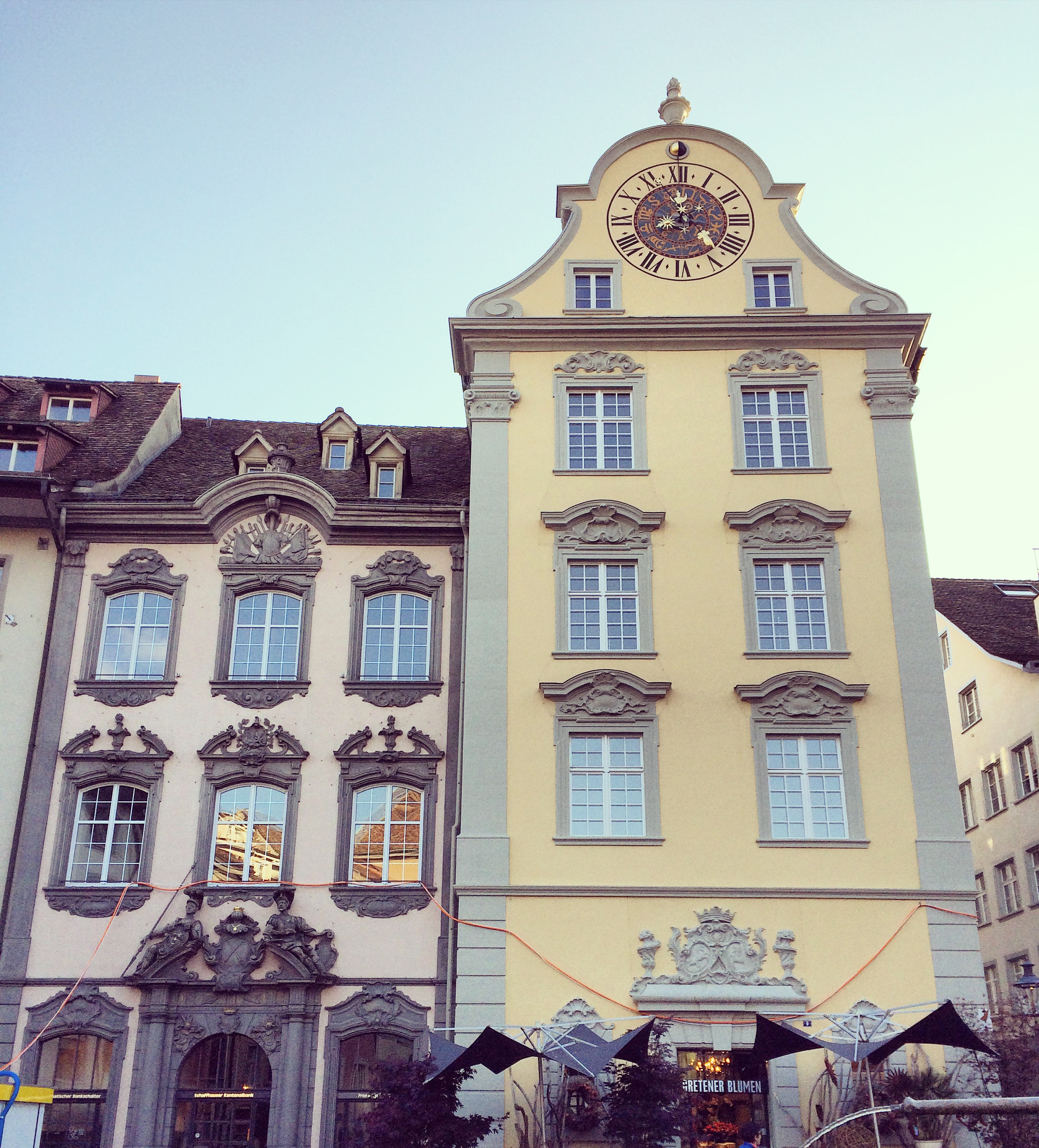 close up of old baroque style house facades, one pink and one yellow