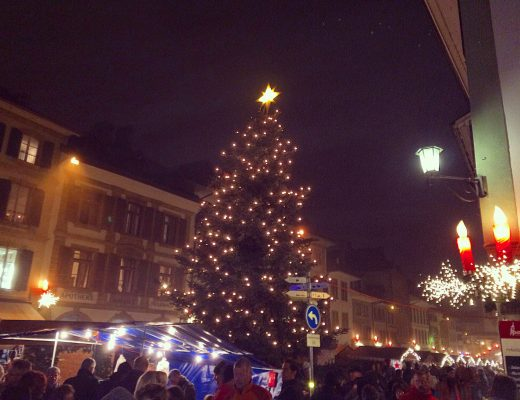 Morat's main square with illuminated Christmas tree surrounded by tiny wooden chalets