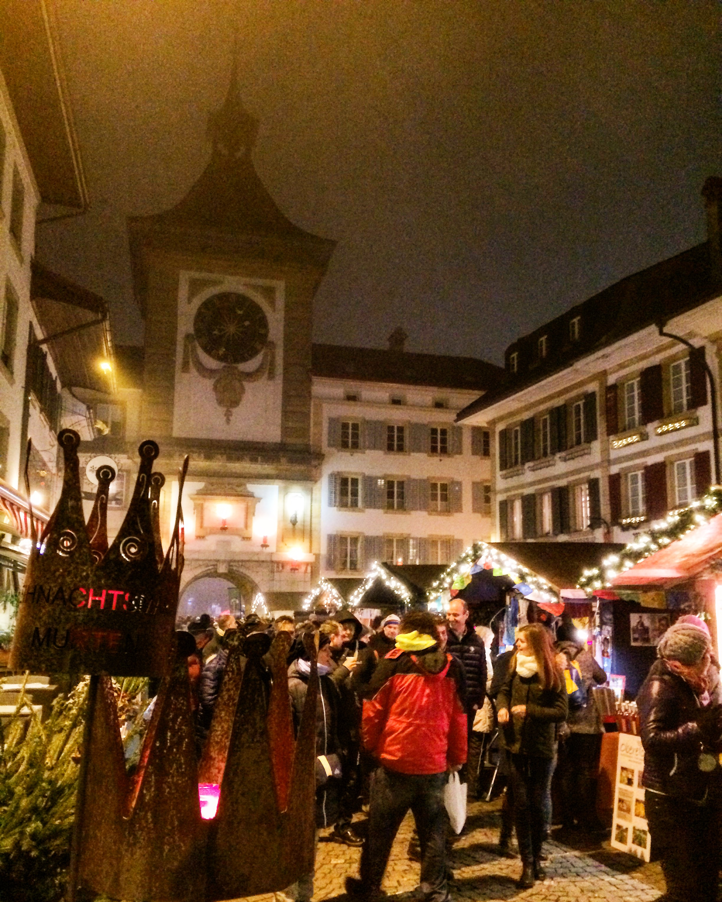 Morat's main square during the Christmas market, filled with people and tiny wood chalets