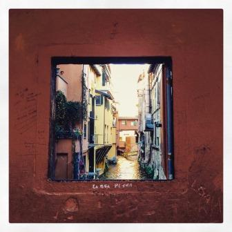 """Terracotta-coloured wall with a window opening on the """"Canale delle Moline"""""""