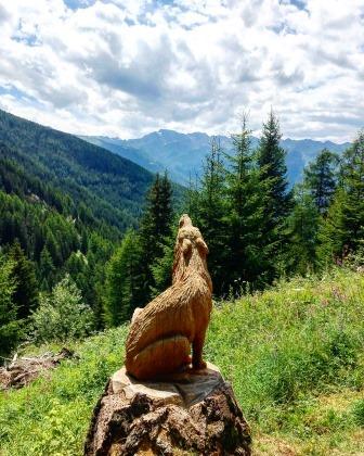 Sculpture de loup en bois au milieu d'un paysage montagnard le long du Bisse de Tsa-Crêta
