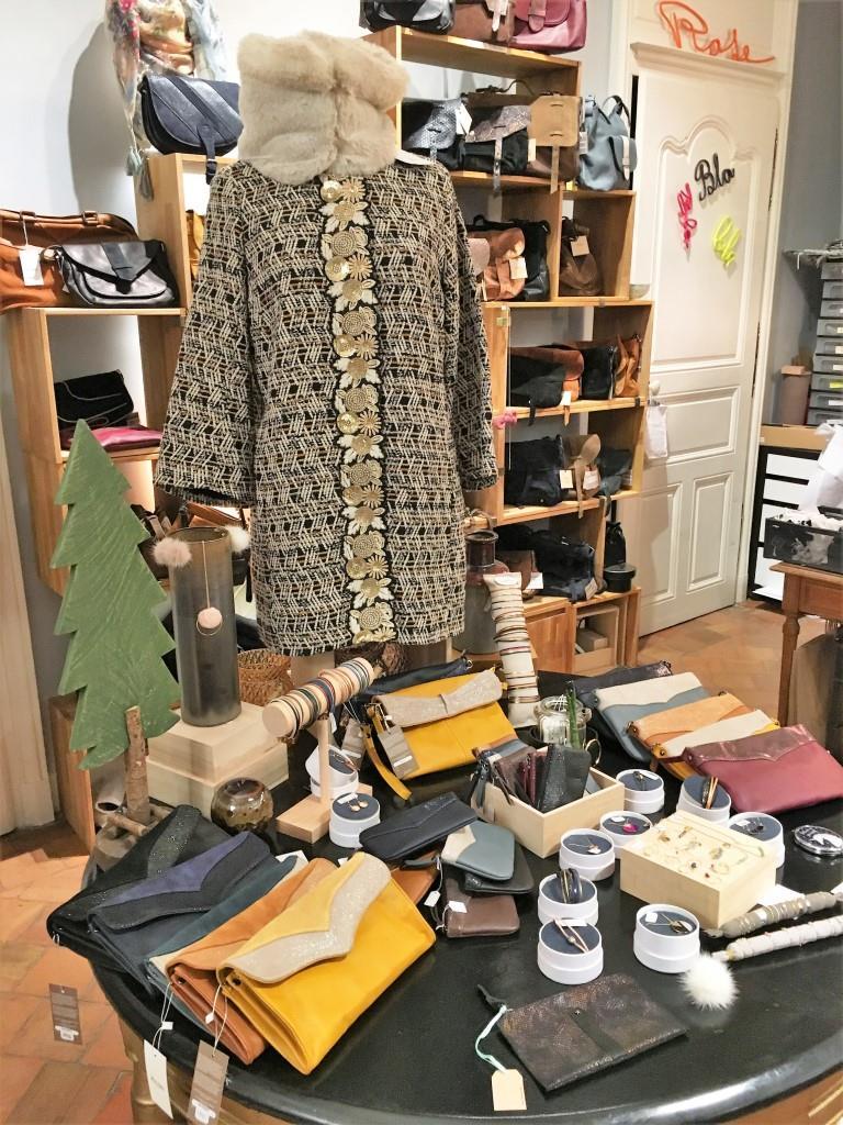 Table dans la boutique Rose à Lyon avec dessus un manteau en broccard navy et or et différents petits accessoires de maroquinerie