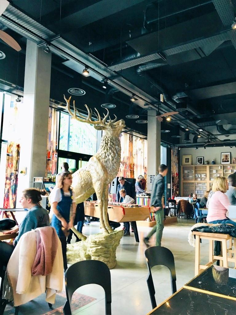 Décor industriel du bar/salle à manger du restaurant du MOB hotel à Lyon avec cerf doré géant au milieu