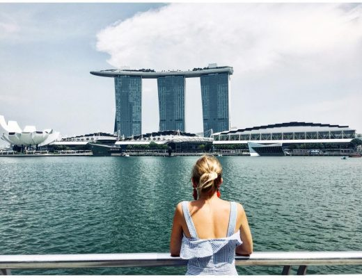 Woman blogger heidigoestravelling leaning against a railing and looking at the Marina Bay Sands hotel