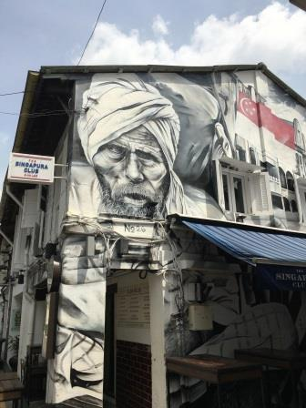 Façade of a house in Haji Lane featuring a bearded old man in black and white