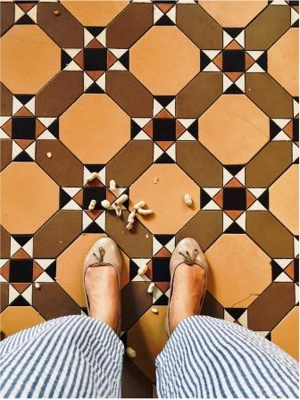 Female blogger heidigoestravelling's feet on terracotta tiles and surrounded by peanuts shells