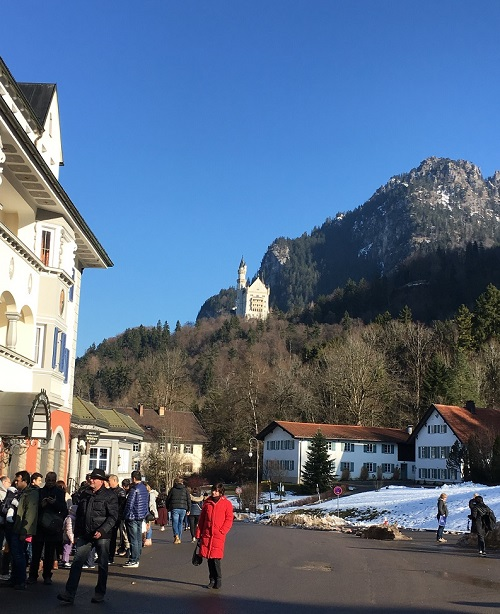 Street in Hohenschwangau with people walking on it and Neuschwanstein castle in the background