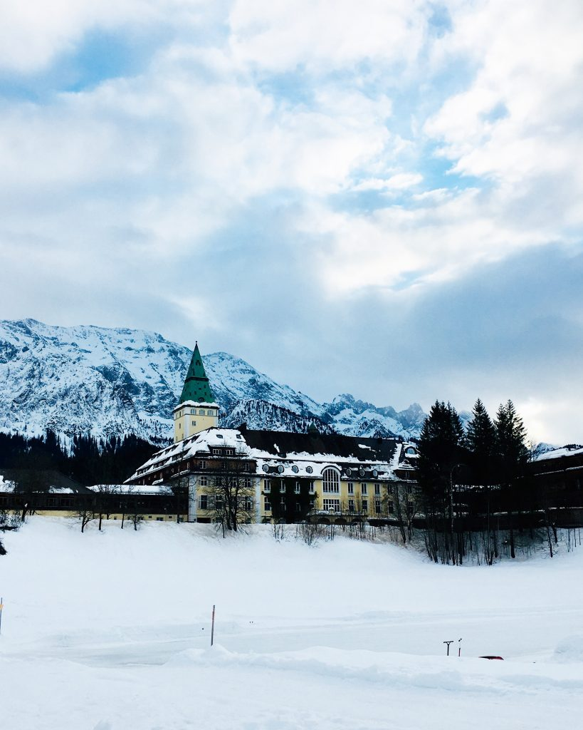 View of the main building of the Hotel Schloss Elmau in front of a snowy mountain