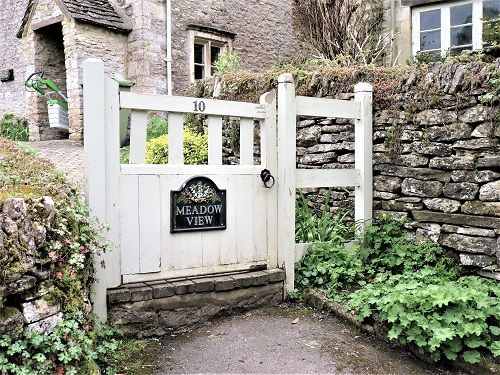 Picture of small white wood gate leading to small stone cottage