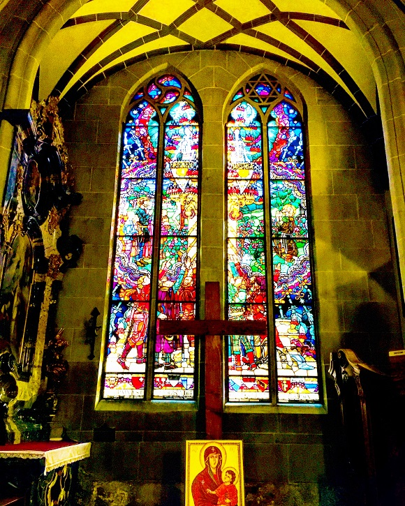 Picture of a large multicoloured stained glass window inside a cathedral.