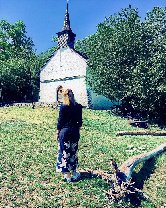 Picture of female blogger heidigoestravelling looking at a small white chapel, next to a log and standing on grass.