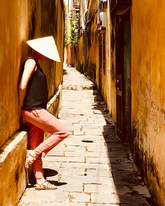 Picture of female blogger heidigoestravelling wearing a traditional Vietnamese pointy hat and standing against a yellow painted wall