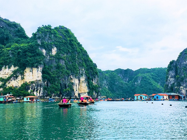 View of a fishing village on Halong Bay's dark green water
