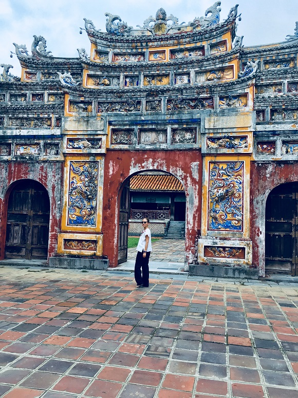 6 reasons to visit Vietnam heidigoestravelling posing in front of gate Purple City Hué