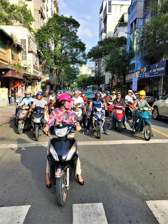 6 reasons to visit Vietnam swarm of scooters Saigon