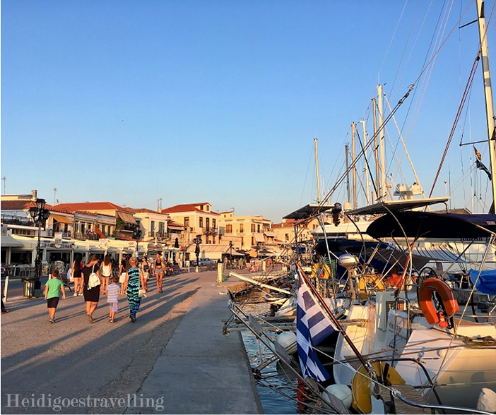 Picture of Aegina's waterfront with on the left side honey-coloured small houses and shops and on the right docked sailing boats