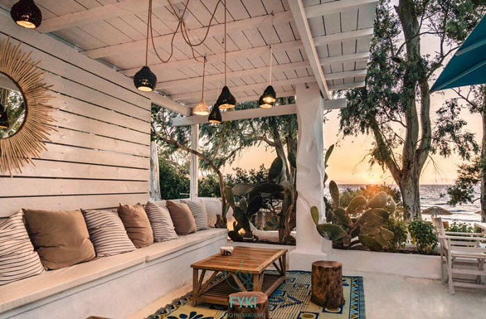 Picture of white-painted wooden structure beach bar in Aegina showcasing taupe-coloured cushions and a big sun-shaped mirror