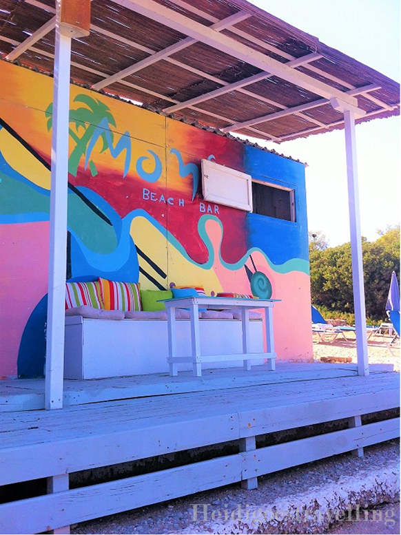 Picture of rainbow-coloured beach bar wall with a small table and medium sized wooden bench in front of it