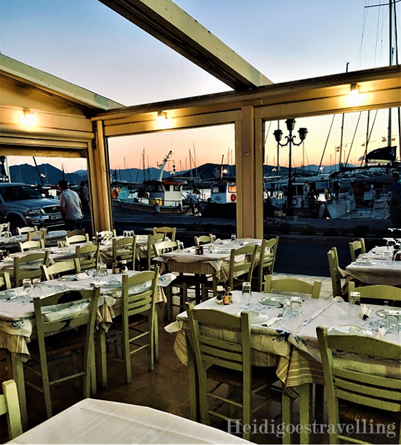 Picture of the terrace of a traditionnal Greek restaurant facing a marina