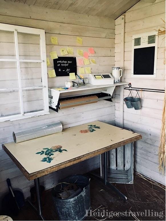 Photo de l'intérieur d'un cabanon en bois montrant une table, une fenêtre, deux rouleaux de papiers emballages, un transparent, un kraft.