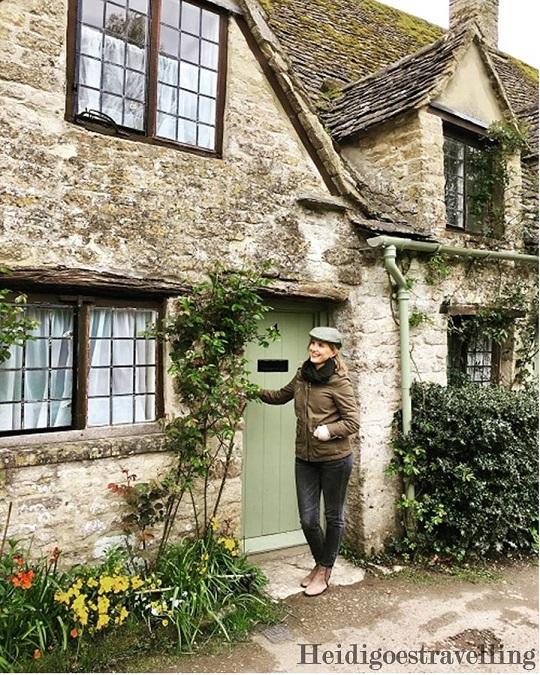 Picture of female blogger heidigoestravelling holding the doorknob of tiny stone cottage