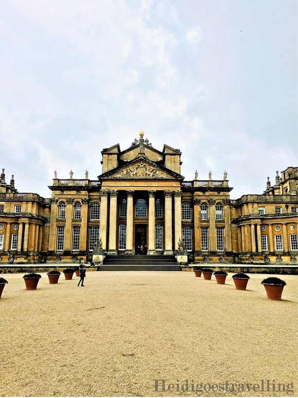 Picture of golden stone neo-classical grand building facing a beige gravel-walk