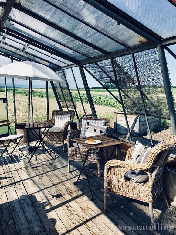Intérieur d'une serre de jardin aménagé avec parquet en planche de bois, fauteuil en osier, parasol et tables de bistrot en bois.
