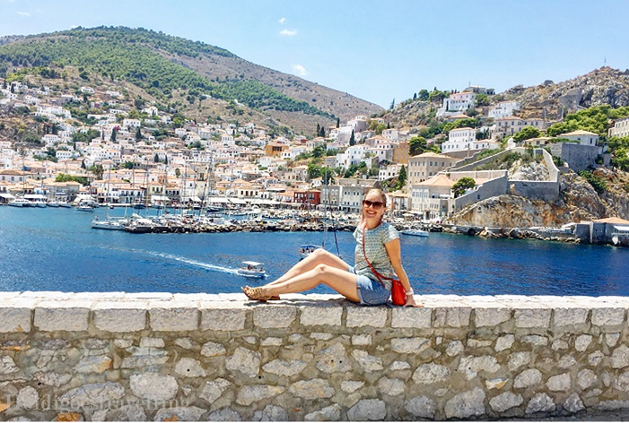 female blogger Heidigoestravelling posing on a low wall with the bay of Hydra town in the background