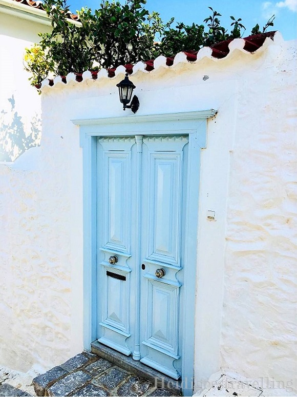 Picture of light blue double-sided door surrounded by white painted wall