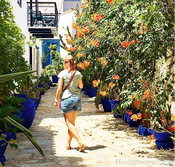Picture of female blogger heidigoestravelling walking on small peppled street ornated with dark blue flower pots and orange flower trees