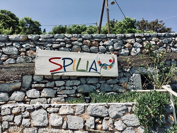 Stone wall with white painted wooden sign with the word SPILIA painted on it
