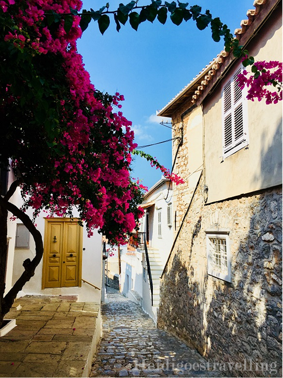 Narrow and peppled village street with pink bougainvillea