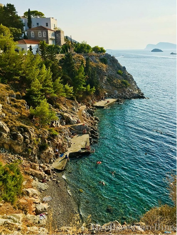 View from a cliff of stony beach and emerald green water