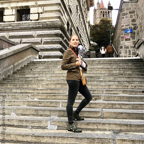 young blond female blogger standing on stone staircase in front of the Lausanne cathedral