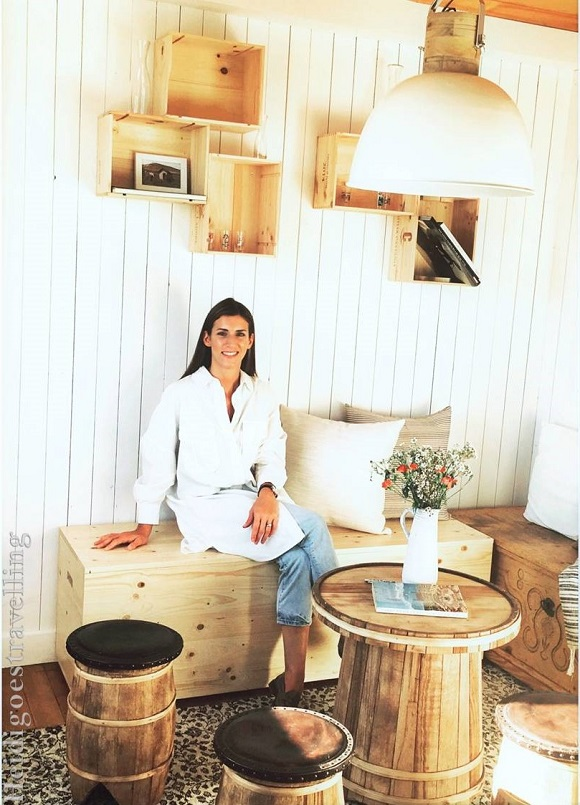 Young woman sitting inside a wooden-built white interior on a wood trunk
