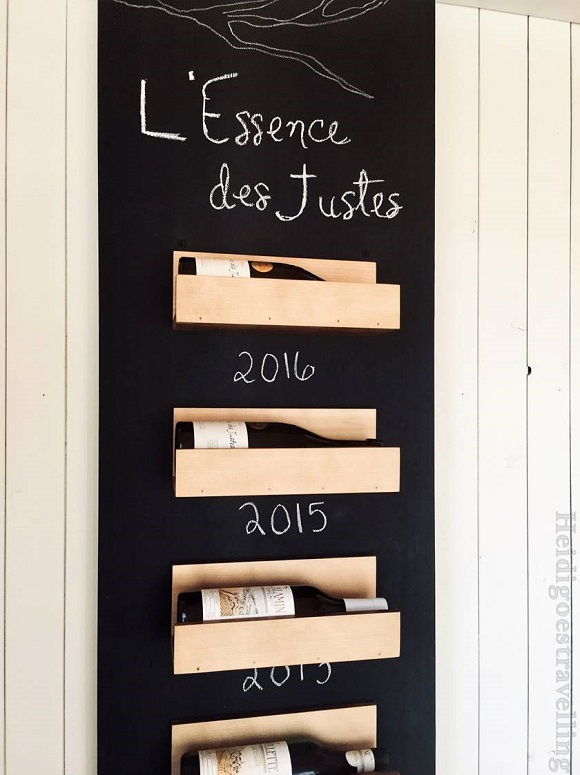 Close-up picture of wineshelf made of chalkboard and small wood containers containing 4 wine bottles