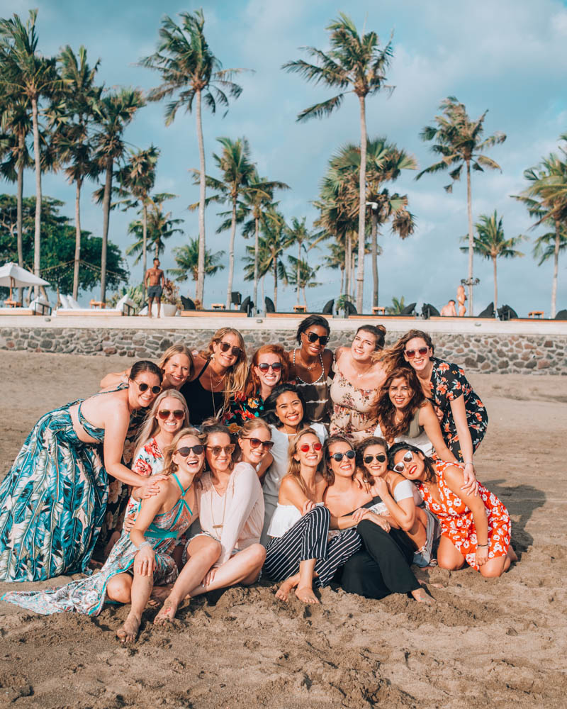 Photo of a group of 17 women posing on a sandy beach