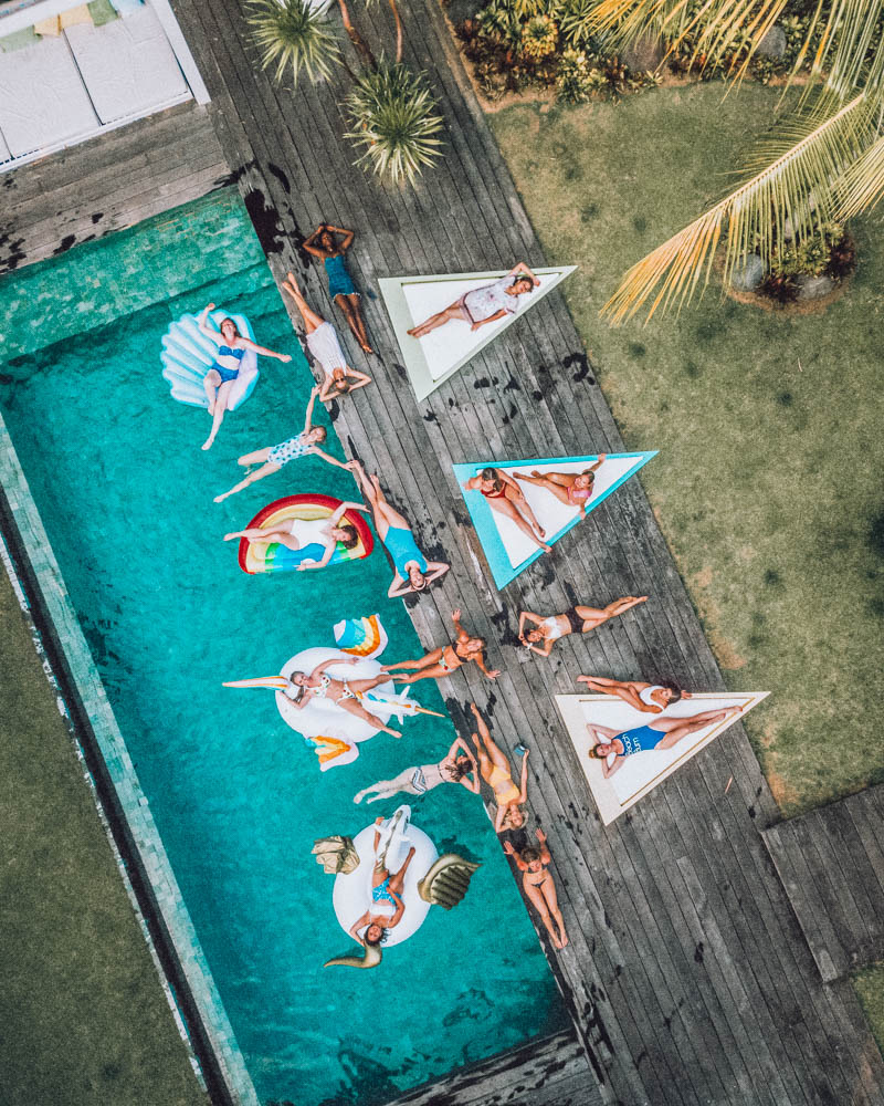 Drone view of 18 women lying on floaties or sunbeds