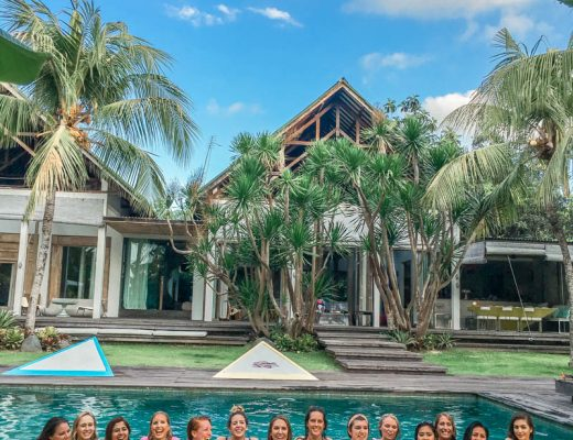 Row of 14 women in a pool in the middle of a lush green garden and in front of a tropical villa