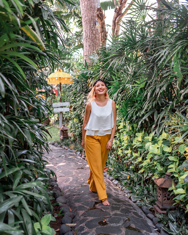 Female blogger heidigoestravelling walking down a stone alley surrounded by lush greenery