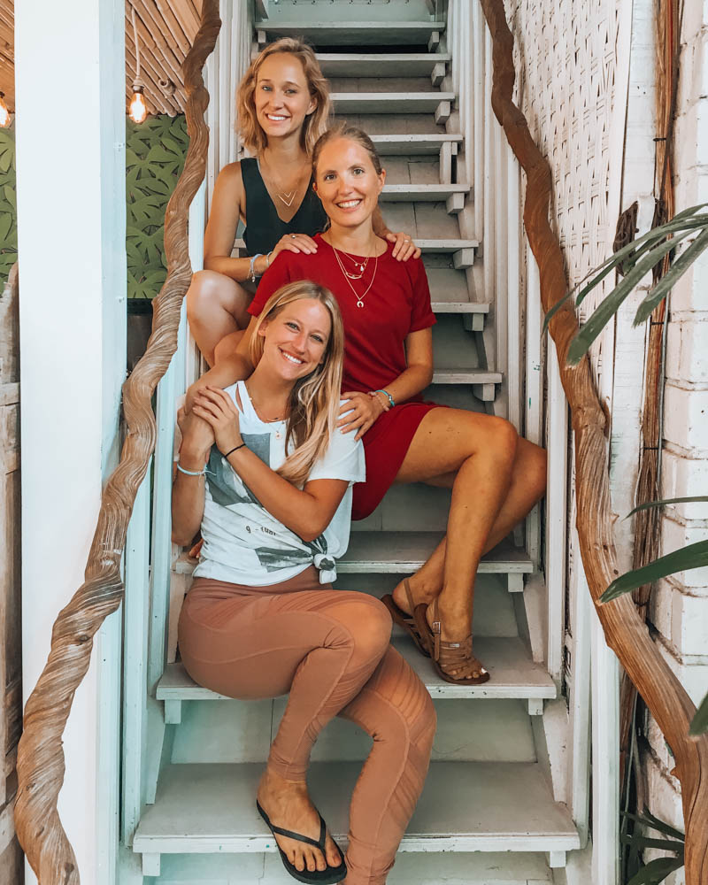 Picture of 3 young and blond women lined up and sitting on a white staircase