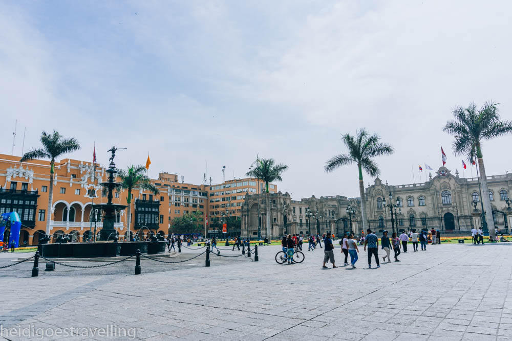 180° view of Plaza de Armas square in Lima with people walking on it and in the background two colonial buildings, one greyish and the other mustard-coloured