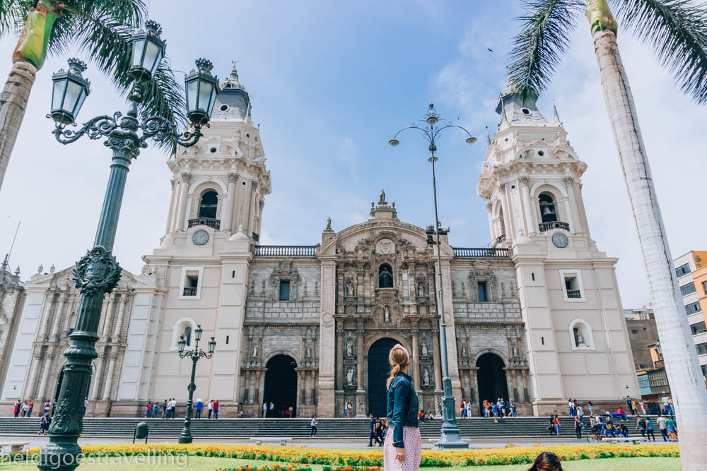 Young blond women standing on a bench and starring at a massive cathedral