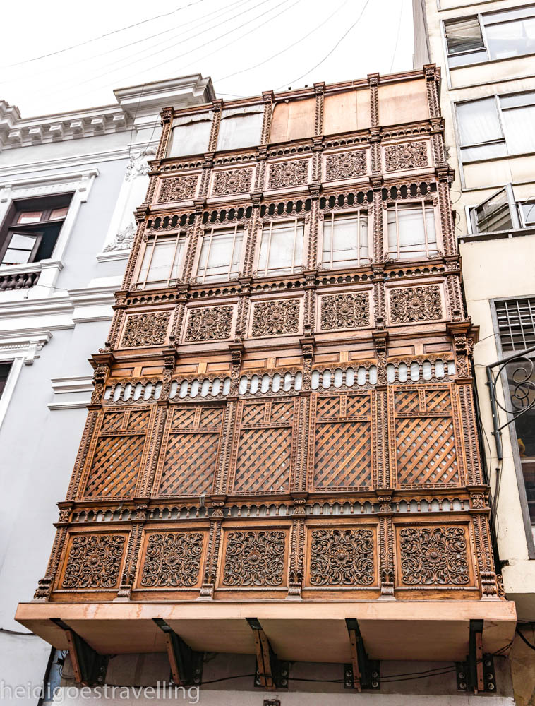 Picture of a intricated wooden-carved balcony from a street in central Lima