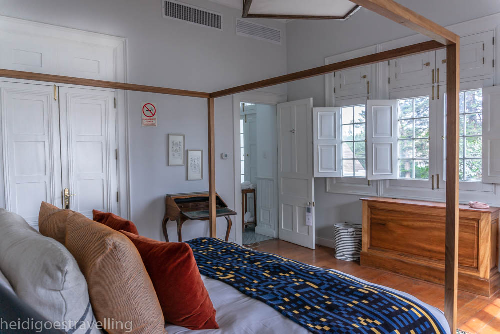 picture of a bedroom with a four poster bed, wood furniture and a door opening on an ensuite bathroom