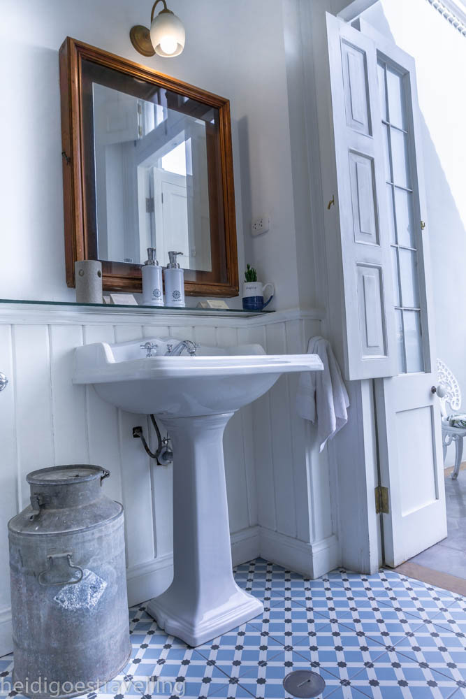 picture of a white bathroom with blue and black tiles and sink and door opening on a small terrace