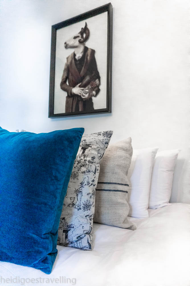 stack of petrol blue, toile de jouy, beige and white cushions on a bed