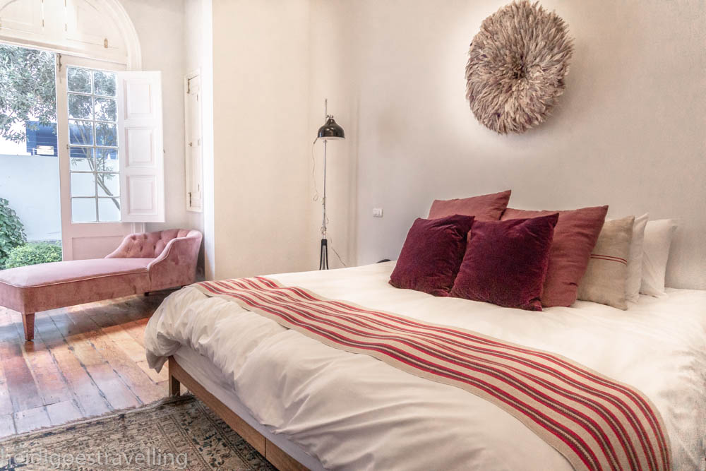 picture of a pink and white themed bedroom with and a door opening on a garden