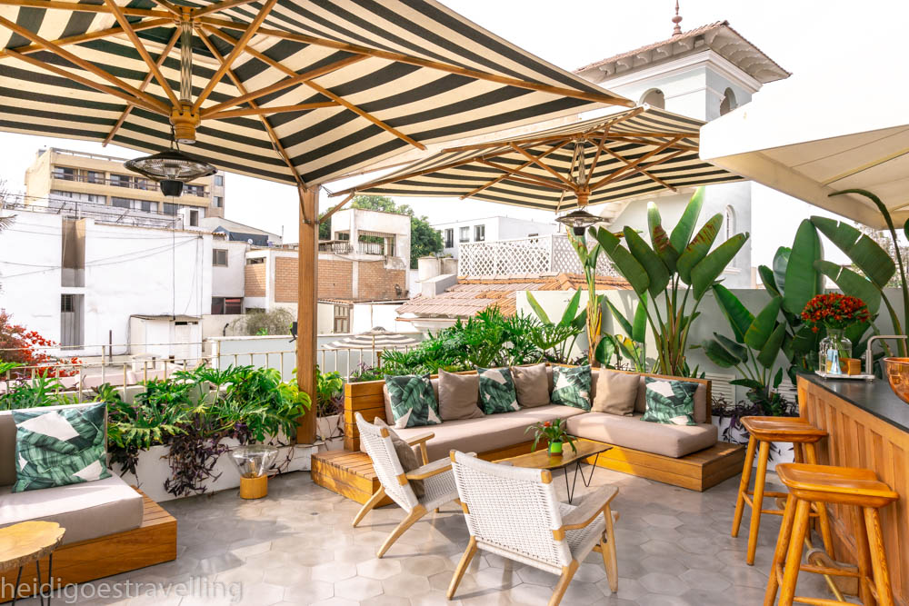 Picture of a rooftop bar with golden coloured wood furniture, lots of greenery and banana leaves printed cushion