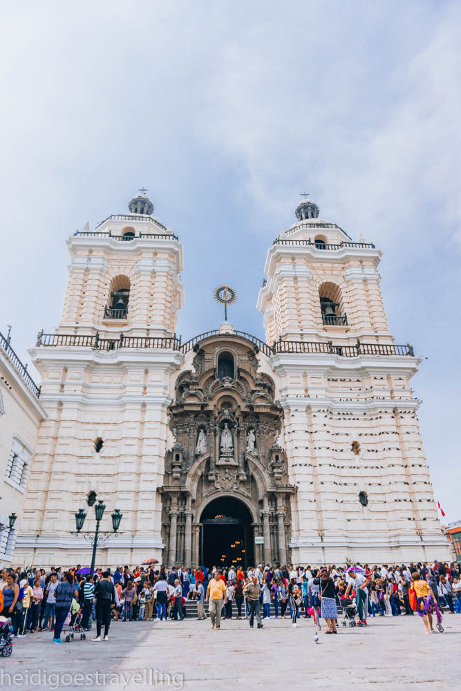 Picture of a baroque style impressive church with a richly sculpted portico and a huge line of people waiting in front of it to enter the church